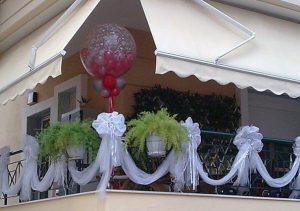 λευκες κορδελες και συνθεση με μπαλονια σε μπαλκονι