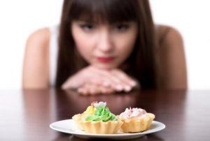 κοπέλα κοιτάζει ένα πιάτο με γλυκά