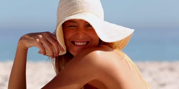 γυναίκα που φοράει καπέλο στην παραλία