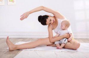 γυναίκα κάνει γυμναστική κρατώντας το μωρό της