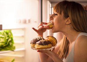 γυναίκα τρώει γλυκά μπροστά στο ψυγείο