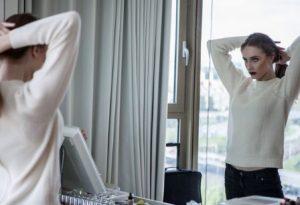 γυναίκα κοιτιέται στον καθρέφτη