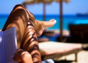κοπελα διαβαζει βιβλιο στην παραλια