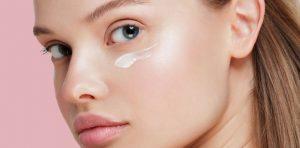 γυναίκα φοράει κρέμα ματιών προϊόντα ομορφιάς ψυγείο