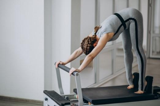 γυναίκα κάνει διάταση κρεβάτι pilates