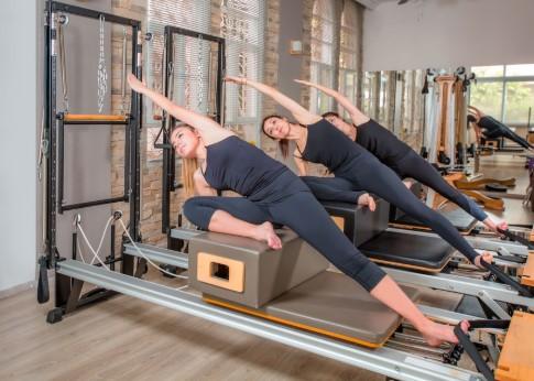 γυναίκες κάνουν έκταση στο πλάι πάνω στο κρεβάτι pilates reformer τέλεια άσκηση