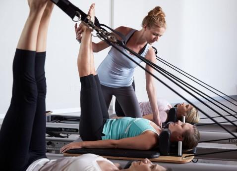 pilates reformer κρεβάτι γυμνάστρια προσέχει τραυματισμούς