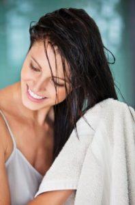 γυναίκα τρίβει μαλλιά με πετσέτα μετά το μπάνιο