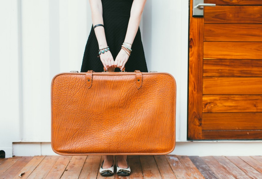 κοπέλα κρατάει καφέ βαλίτσα ταξίδι