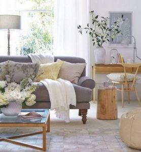 γκρι καναπές με άσπρο ριχτάρι και μπεζ πουφ
