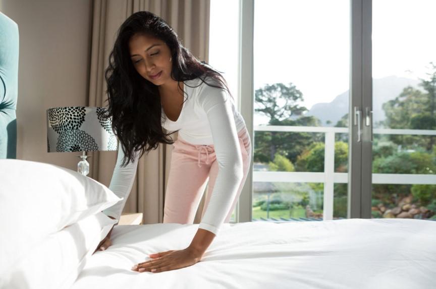 γυναίκα στρώνει κρεβάτι σεντόνια