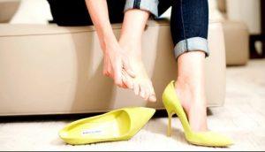 γυναίκα τρίβει πόδι κίτρινη γόβα