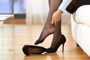 γυναίκα βγάζει μαύρη γόβα πονάνε πόδια