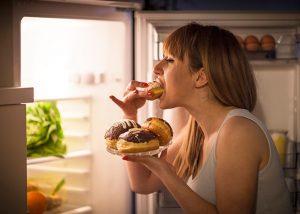 κοπέλα τρώει μπροστά στο ψυγείο