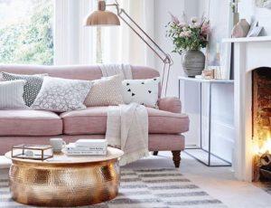ροζ καναπές με άσπρο ριχτάρι και χρυσό τραπεζάκι