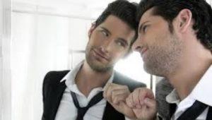 άντρας κοιτάζει στον καθρέφτη και χαμογελάει