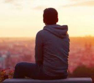 άντρας μόνος σε παγκάκι κοιτάζει ηλιοβασίλεμα