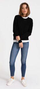 γυναίκα με μαύρο πουλόβερ jean και άσπρα sneakers