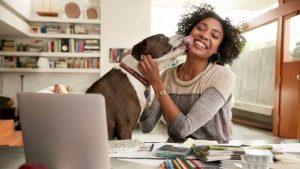 γυναίκα γελώντας παίζει με τον σκύλο της