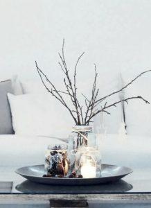 Διακόσμησε το τραπεζάκι στο σαλόνι ή το καθιστικό σου με κλαδιά, μικρά φωτάκια (ή κεράκια) και γυάλινα βαζάκια τοποθετώντας είτε κουκουνάρια, είτε φύλλα δέντρων ή ακόμα και τα κεράκια.