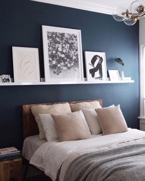 ράφι με πίνακες πάνω από το κρεβάτι μπλε τοίχος