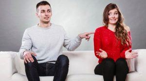 άντρας ακουμπάει γυναίκα καθιστοι στον καναπέ