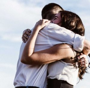 άντρας και γυναίκα αγκαλιάζονται σφυχτά