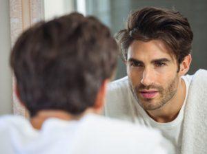 άντρας κοιτάζεται στον καθρέπτη