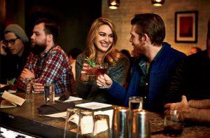 γυναίκα άντρας τσουγκρίζουν ποτήρια μπαρ