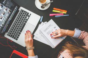γυναίκα δουλέυει στον υπολογιστή κρατάει σημειώσεις