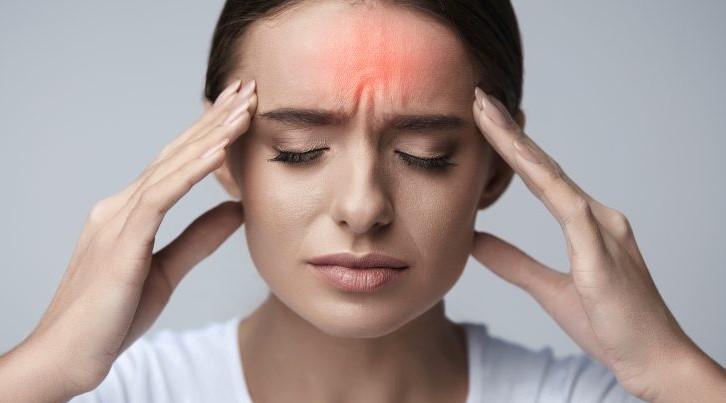 γυναίκα πιάνει το κεφάλι της πονάει