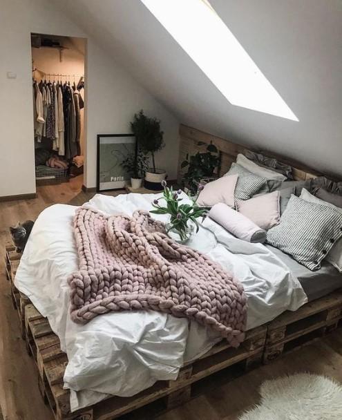 κρεβάτι από παλέτες με πολλά μαξιλάρια και κουβέρτες