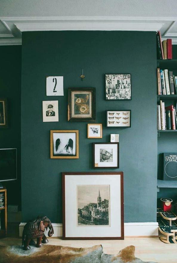 σκούρος πράσινος τοίχος με διακοσμητικά κάδρα