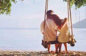 ζευγάρι κάθεται σε κούνια στην παραλία
