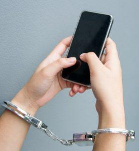 χέρια με χειροπέδες και κινητό