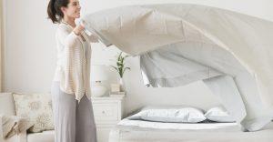γυναίκα αλλάζει σεντόνια κρεβάτι προστατεύσεις σπίτι μικρόβια