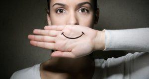 γυναίκα κρύβει συναισθήματα παλάμη ζωγραφισμένο χαμόγελο