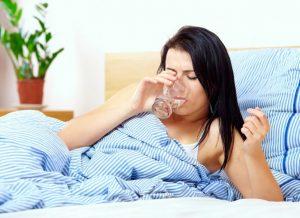 γυναίκα ξαπλωμένη πίνει νερό ξεπεράσεις γρίπη