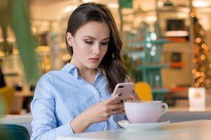 γυναίκα πίνει καφέ ασχολείται με το κινητό τον ξεχάσεις