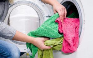 γυναίκα βάζει πλυντήριο πολύχρωμες πετσέτες