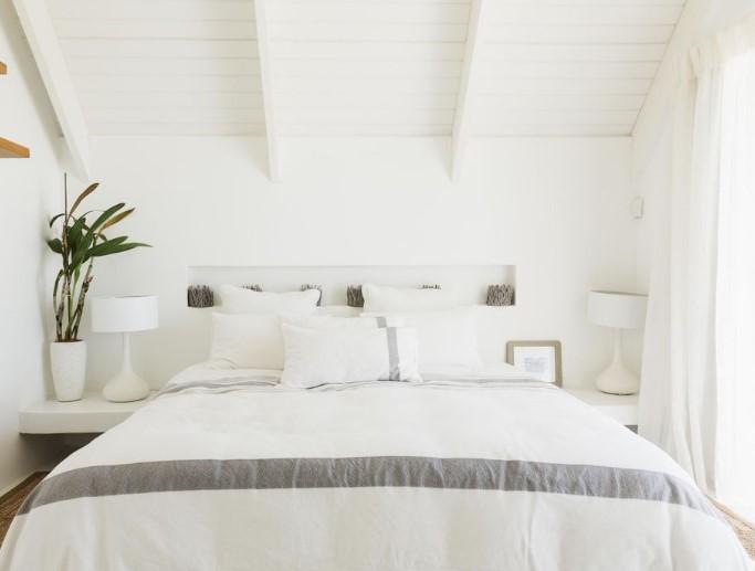 Κρεβάτι σε κρεβατοκάμαρα με άσπρη διακόσμηση