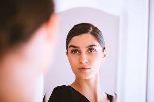 μελαχρινή γυναίκα κοιτιέται στον καθρέπτη πως είσαι εξωτερικά