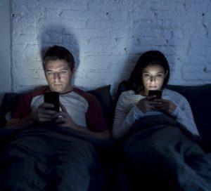 ζευγάρι στα κινητά στο κρεβάτι