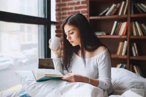 γυναίκα διαβάζει βιβλίο κρεβάτι πίνει καφέ περάσεις μέρα σπίτι