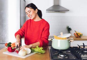 γυναίκα κόβει λαχανικά μαγειρεύει