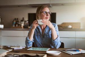 γυναίκα πίνει καφέ πριν την εργασία από το σπίτι
