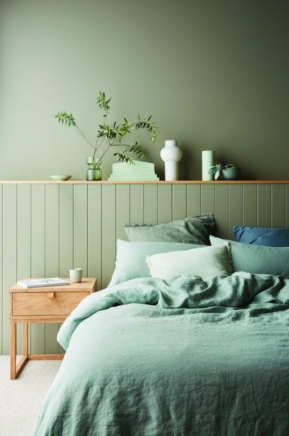 κρεβάτι πράσινος τοίχος πράσινα σεντόνια