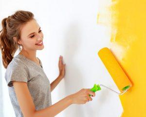 χαμογελαστή κοπέλα βάφει τον τοίχο