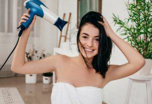 χαρούμενη γυναίκα με σεσουάρ