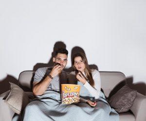 ζευγάρι τρώει ποπ κορν βλέπει τηλεόραση